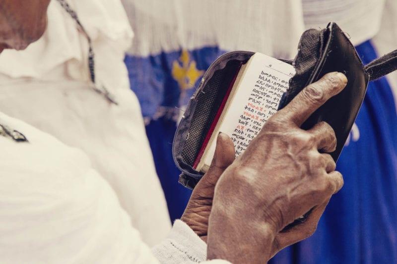 Fiel lendo a Bíblia em amárico, a língua da Etiópia